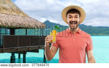 summer, vacation and people concept - happy smiling young man in straw hat with orange juice cocktail over bungalow on tropical beach background in french polynesia