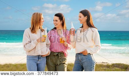 travel, tourism and friendship concept - group of happy young women or female friends with non alcoholic drinks talking over tropical beach background in french polynesia