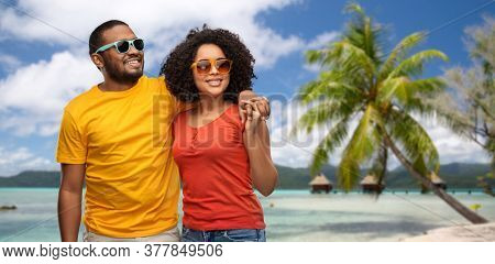 summer, relationships and people concept - happy african american couple in sunglasses over tropical beach background in french polynesia