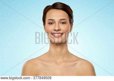 beauty, bodycare and people concept - beautiful young woman with bare shoulder over blue background