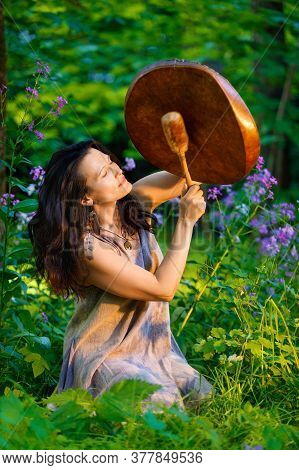 Shaman Woman Playing Her Shaman Sacred Drum Among The Flowers In The Forest Against The Background O
