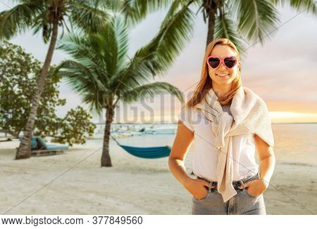 travel, tourism and vacation concept - happy woman in heart-shaped sunglasses over tropical beach background in french polynesia