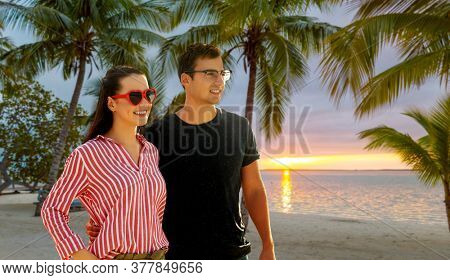 travel, tourism and vacation concept - happy couple hugging over tropical beach background in french polynesia
