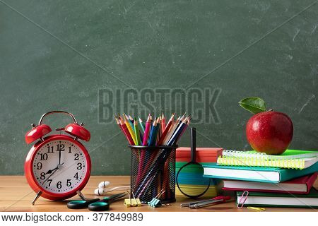 Alarm Clock, School Supplies And Fresh Red Apple Against Blackboard Background. Back To School Or Ed