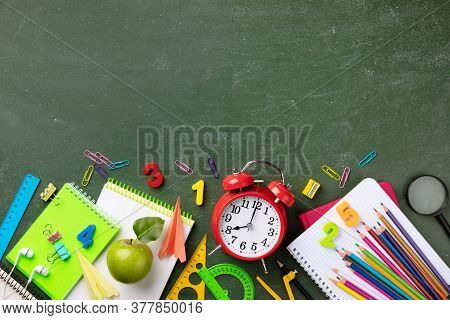 Back To School And Education Concept With Alarm Clock, School Supplies And Fresh Green Apple On Blac