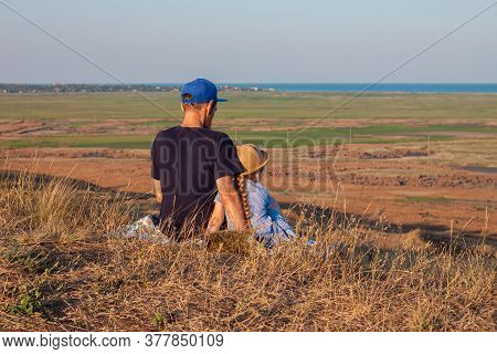 Father And Daughter Sitting By Lakes On A Nature Lanscape. A Little Girl With Long Blond Hair Braid