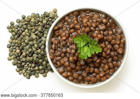 Cooked French Green Puy Lentils With Garnish In White Ceramic Bowl Next To Dry Lentils Isolated On W
