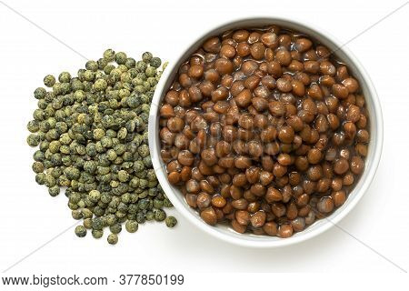 Cooked French Green Puy Lentils In White Ceramic Bowl Next To Dry Lentils Isolated On White. Top Vie