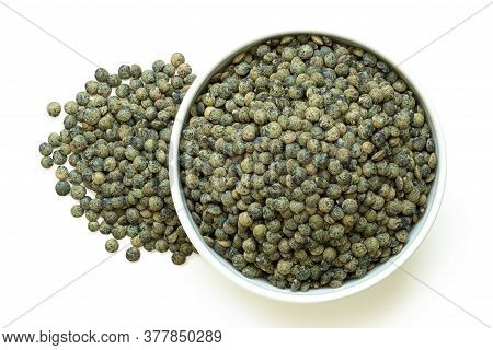 Dry French Green Puy Lentils In White Ceramic Bowl Next To Pile Of Lentils Isolated On White. Top Vi