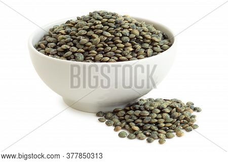 Dry French Green Puy Lentils In White Ceramic Bowl Next To Pile Of Lentils Isolated On White. High A