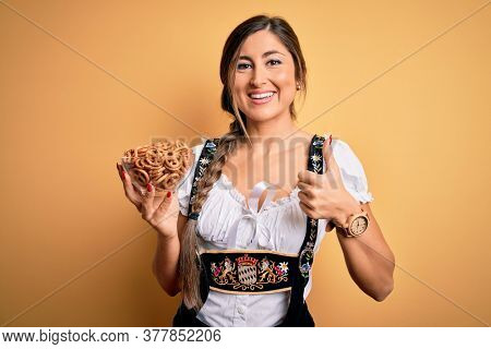 Young brunette german woman wearing traditional Octoberfest dress holding bowl with pretzels happy with big smile doing ok sign, thumb up with fingers, excellent sign