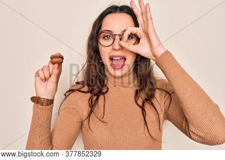 Young beautiful woman with blue eyes wearing glasses eating french dessert macaron with happy face smiling doing ok sign with hand on eye looking through fingers