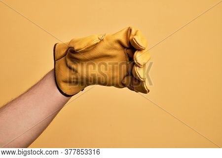 Hand of caucasian young man with gardener glove over isolated yellow background holding invisible object, empty hand doing clipping and grabbing gesture
