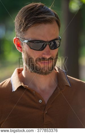 Handsome Bearded Man In Sunglasses Looks Around, Close-up. Summer Season In The Park.