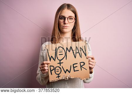 Young beautiful redhead woman asking for women rights holding banner over pink background with a confident expression on smart face thinking serious