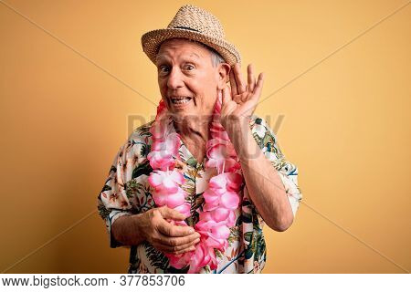 Grey haired senior man wearing summer hat and hawaiian lei over yellow background smiling with hand over ear listening an hearing to rumor or gossip. Deafness concept.
