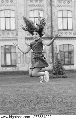 Girl Jumping Outdoors. Feel Free. Jump Of Happiness. Small Girl Jump On Green Grass. Full Of Energy.