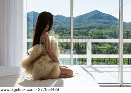 Attractive Young Woman Wrapped In A Fur Coat Sitting In Hotel Room. Portrait Of Sensual Female Daydr