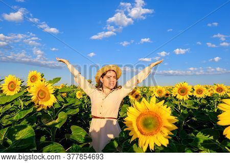 Smiling Woman In Straw Hat In Blooming Sunflower Field With Outstretched Arms