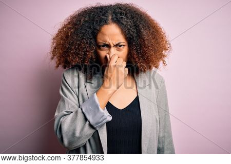 Young african american businesswoman with afro hair wearing elegant jacket smelling something stinky and disgusting, intolerable smell, holding breath with fingers on nose. Bad smell