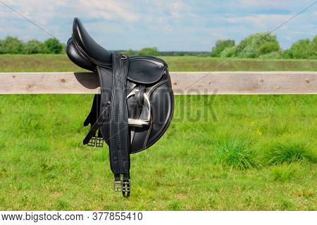 The Black Saddle And Its Girth Is Lying On The Wooden Hitching Post In Outdoors.