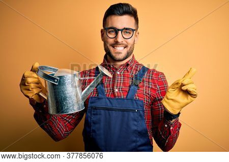 Young gardener man wearing working apron and gloves holding watering can very happy pointing with hand and finger to the side