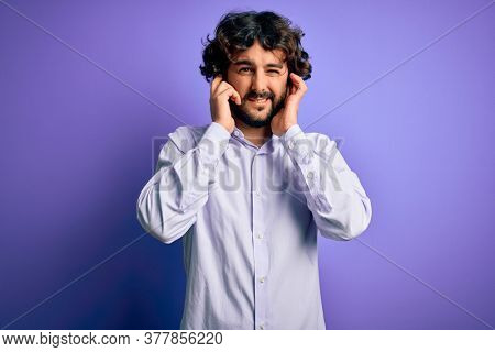 Young handsome business man with beard wearing shirt standing over purple background covering ears with fingers with annoyed expression for the noise of loud music. Deaf concept.