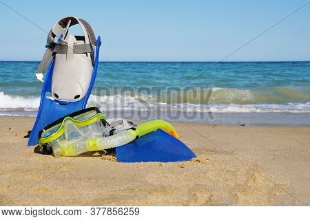 Flippers And Mask For Swimming On The Sand Against The Background Of The Sea And Clear Sky, Copy Spa