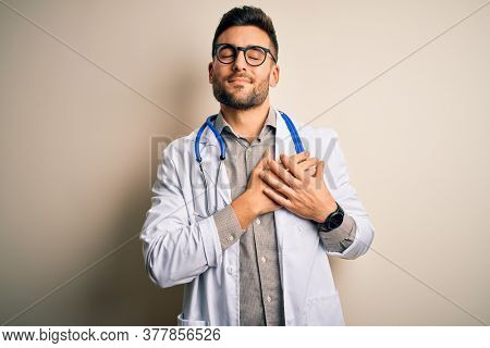 Young doctor man wearing glasses, medical white robe and stethoscope over isolated background smiling with hands on chest with closed eyes and grateful gesture on face. Health concept.