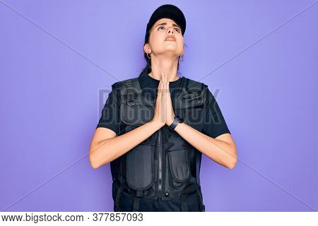 Young police woman wearing security bulletproof vest uniform over purple background begging and praying with hands together with hope expression on face very emotional and worried. Begging.