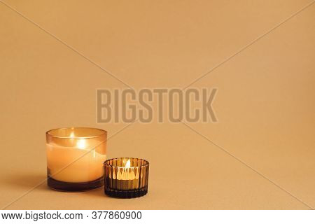 Two Burning Aroma Candles With Ginger Scent On Orange Background. Autumn Mood