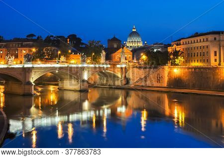 Victor Emmanuel Bridge Over Tiber River With St. Peter's Cathedral As Background At Night, Rome, Ita