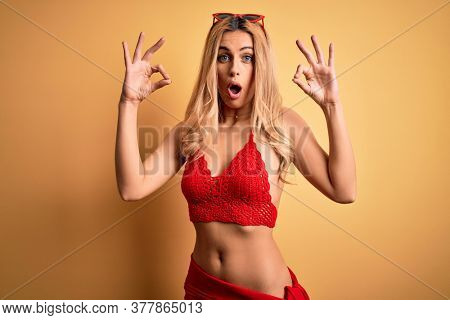 Young beautiful blonde woman on vacation wearing bikini over isolated yellow background looking surprised and shocked doing ok approval symbol with fingers. Crazy expression
