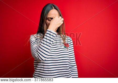 Young beautiful blonde woman with blue eyes wearing glasses standing over red background tired rubbing nose and eyes feeling fatigue and headache. Stress and frustration concept.