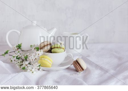 Tasty French Macarons And A Tea-set With Blossoming Branches On A White Background.   Pastel Colors.