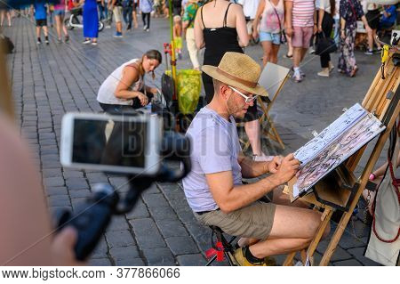 Prague - July 20, 2019: Street Caricature Artist Drawing Tourists While Being Filmed By A Smartphone