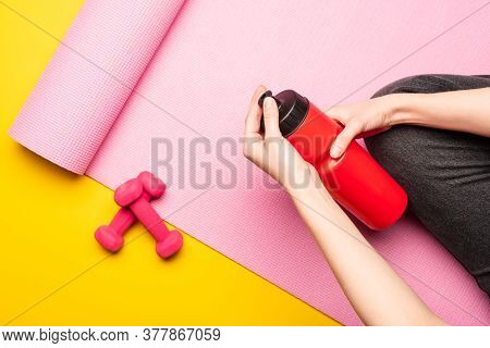 Partial View Of Woman Holding Sports Bottle While Sitting On Pink Fitness Mat Near Dumbbells On Yell
