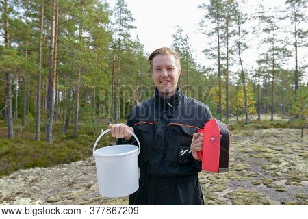 Portrait Of Happy Young Handsome Man Holding Bucket And Berry Picker In The Forest