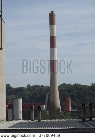Obsolete Industry, Factory Chimney With Blue Sky In The Background