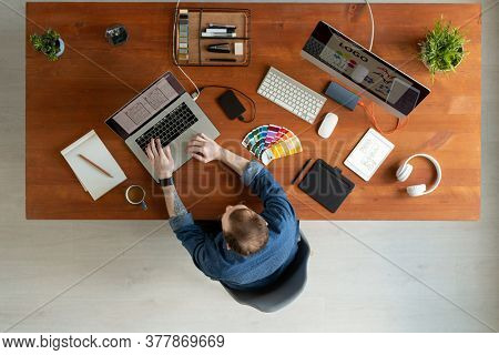 Directly above view of man with tattoo sitting at wooden table and editing ui design on laptop