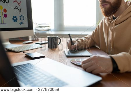 Close-up of busy brand designer sitting at desk and creating graphic design using digitizer and color palette