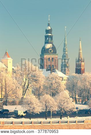 Buildings And Trees Are Covered With White Frost In The City Of Riga. The Spiers Of The Churches Gli