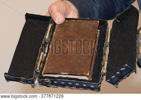 Person Holding An Antiquarian Book, Which Is Put In A Case, In His Hand