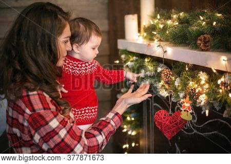 Beautiful Mother In A Plaid Shirt Holds Her Daughter In A Red Dress In Her Arms. They Watch And Touc