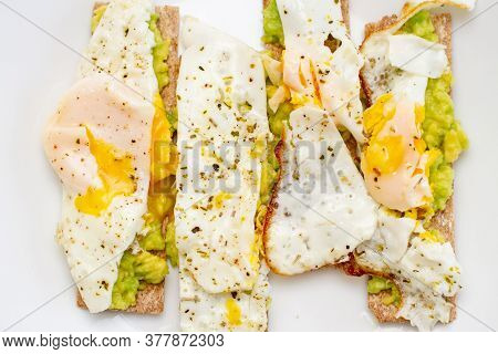 Avocado And Poached Egg Sandwiches On White Plate, Top View. Healthy Breakfast Vegan Toast. Vegetari