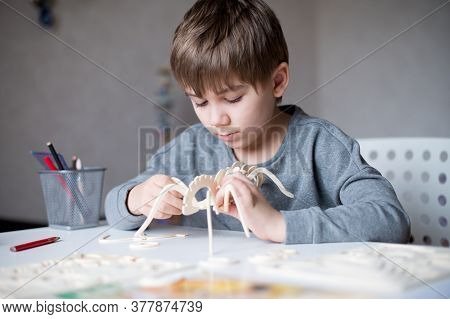 A Boy Enthusiastically Makes A Wooden Toy At His Table In The Room In His Room