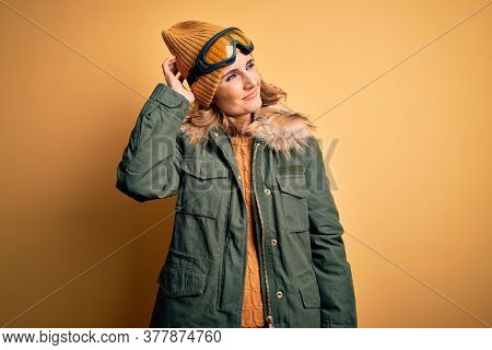 Middle age beautiful blonde skier woman wearing snow sportwear and ski goggles confuse and wondering about question. Uncertain with doubt, thinking with hand on head. Pensive concept.