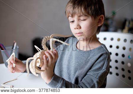 Close-up Of A Boy Assembling A Wooden Toy From Parts According To The Instructions