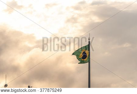 Flag Of Brazil Fluttering In The Wind Hoisted On Iron Mast On Light And Outdoors Background