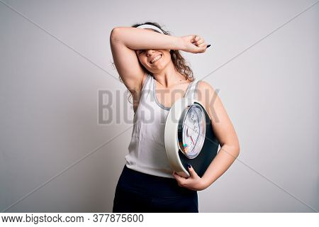 Young beautiful woman with curly hair holding weighing machine over white background Smiling cheerful playing peek a boo with hands showing face. Surprised and exited